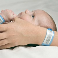 A baby holding her mother's thumb, both wearing hospital ID bracelets --- Image by © Vladimir Godnik/fstop/Corbis