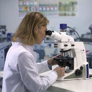woman working on a microscope  Eine Anwenderin sitzt an dem Mikroskop