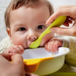 young mother feeding baby baby food with a spoon