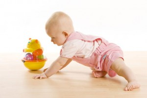 baby girl crawling towards a toy on the floor