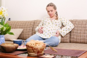 Беременная женщина сидит на диване